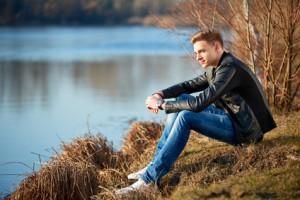Junger Mann mit schwarzer Lederjacke und blauer Jeans