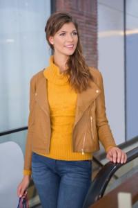 Dame mit hellbrauner jacke und gelbem Wollpullover