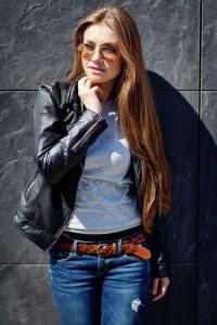 Junge Frau mit schwarzer Lederjacke, Bluejeans, braunem Gürtel und weißem Oberteil